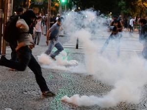 Manifestante chuta bomba de efeito moral na direção dos policiais (Foto: Vanderlei Almeida/AFP)