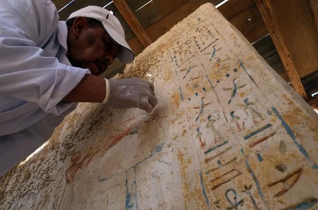 Arqueólogo trabalha no interior de tumba encontrada a 20 km do sul do Cairo, no Egito (Foto: Khaled Desouki/AFP)