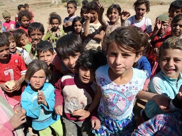 Crianças sírias posam para foto em capmo de refúgiados de Balbeek, na Líbano (Foto: Hussein Malla/AP)