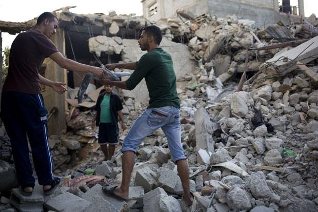 Palestinos passam parte de míssil que atingiu casa no campo de refugiados de Jebaliya em Gaza nesta segunda-feira (4) (Foto: Dusan Vranic/AP)