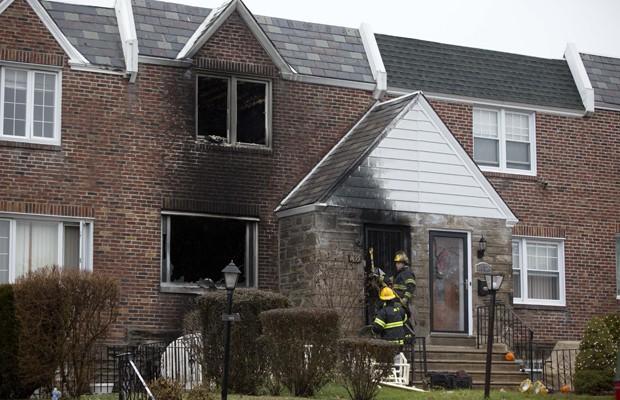 Bombeiros caminham pela casa incendiada na Filadélfia, nesta terça (9) (Foto: Matt Rourke/AP)