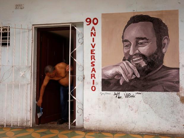 Morador de Havana, Cuba, limpa o chão de sua casa que tem imagem de Fidel Castro  (Foto: REUTERS/Stringer)