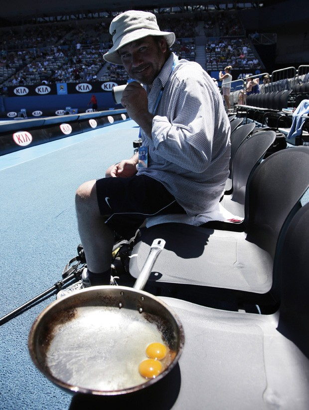 Fotógrafo é visto ao lado de panela fritando ovos durante torneio de tênis em Melbourne, na Austrália (Foto: Rick Rycroft/AP)