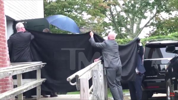 A cantora Taylor Swift escondidas por seus seguranças enquanto é vaiada por seus fãs no casamento da amiga (Foto: Reprodução/TMZ)