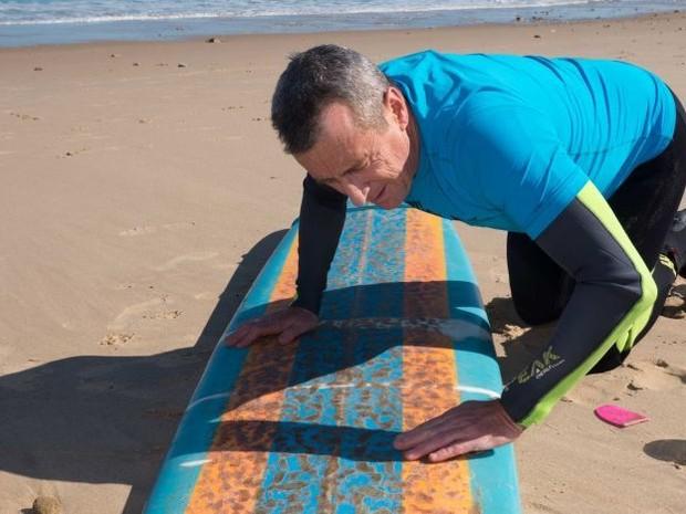 Neil Campbell aplicando a mistura que promete afastar tubares dos surfistas (Foto: Divulgao)