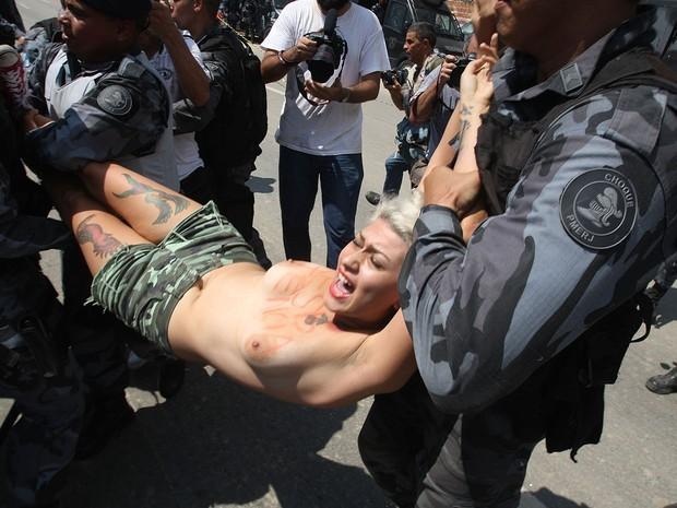 Policiais carregam embaixadora do Femem no Brasil, detida em ato no Maracanã (Foto: Tasso Marcelo/ Estadão Conteúdo)