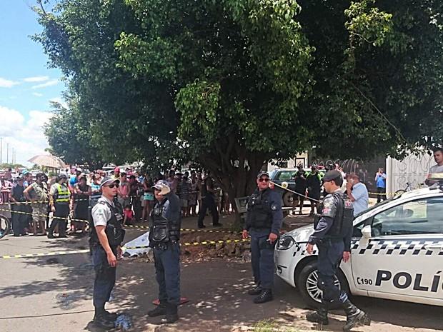 Sob o olhar de curiosos, policiais bloqueiam área onde homem foi morto após reagir a assalto  (Foto: Mateus Rodrigues/G1)