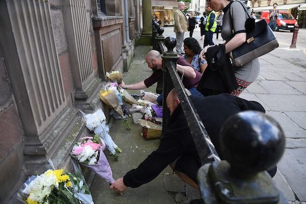 Pessoas deixam flores nos arredores do local no qual ocorreu o atentado no show da cantora Ariana Grande (Foto: Getty Images)