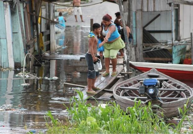 Moradores do bairro da Raiz, na Zona Sul de Manaus, tentam se locomover nas áreas alagadas (Foto: Carlos Eduardo Matos/G1)