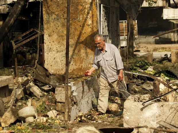 Homem inspeciona destroços após bombardeios do sábado. Neste domingo, ataque a escola deixou mais nove mortos (Foto: Rami Zayat/Reuters)