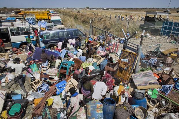 Civis que fugiram de suas casas devido aos conflitos na região amontoam seus pertences em frente ao portão do complexo da Missão da ONU no Sudão do Sul (Foto: Mackenzie Knowles-Coursin/AP)