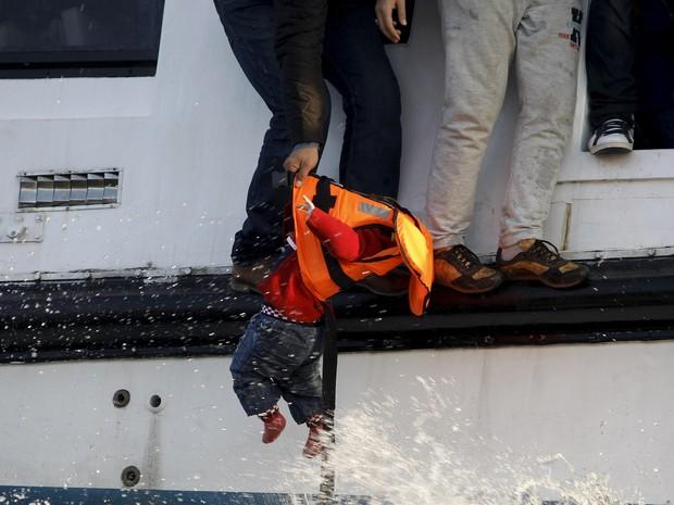Um refugiado se prepara para entregar uma criança a um salva-vidas voluntário na ilha de Lesbos, na Grécia. O barco que eles estavam começou a afundar após atravessar o mar Egeu. Cerca de 150 imigrantes estavam a bordo, a maioria sírios. Não houve vítimas (Foto: Giorgos Moutafis/Reuters)
