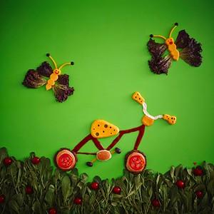 Bike Burger: Uma bicicleta com rodas de hambúrguer e detalhes em queijo prato, ketchup, mostarda, maionese e tomate passei pelo cenário ao lado de borboletas feitas de queijo e alface, com anteninhas de azeitonas (Foto: Divulgação)