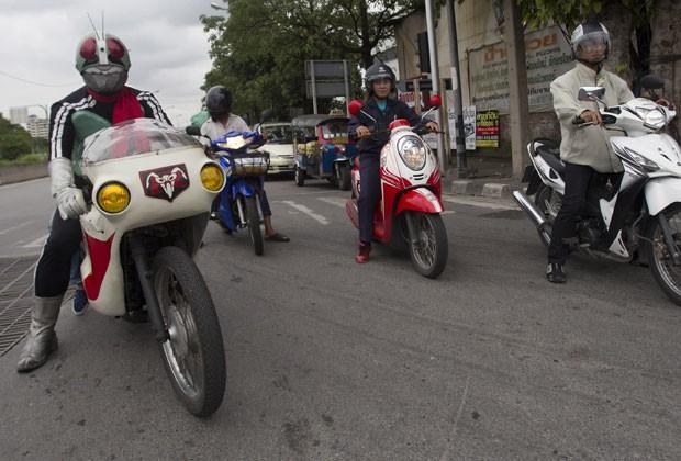 O empresário japonês usou uma moto para andar pelas ruas da cidade (Foto: Sakchai Lalit/AP)