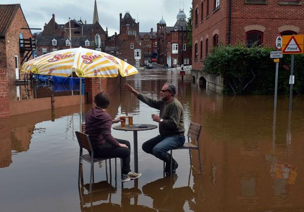 Homens ignoraram o alagamento e foram flagrados bebendo cerveja. (Foto: Paul Ellis/AFP)