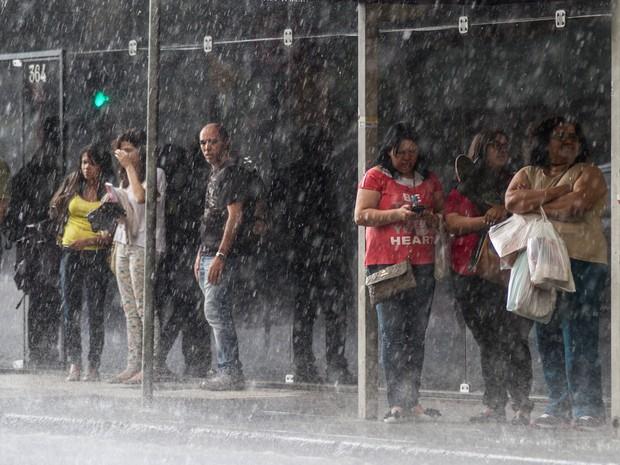 Pedestres se protegem de temporal nos arredores da estação São Bento do Metrô, na região central de São Paulo, nesta sexta-feira (07) (Foto: Dario Oliveira/Estadão Conteúdo)
