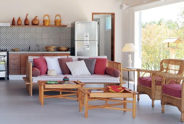O sofá de madeira, da Conceito Firma Casa, é utilizado pela moradora para relaxar. Mesa de centro da Marcenaria Trancoso e livros da Livraria Cultura (Foto: Casa e Jardim)