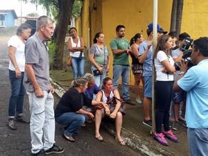 Pais de Larissa aguardam notícias sobre o caso do lado de fora da delegacia em Extrema (Foto: Régis Melo)