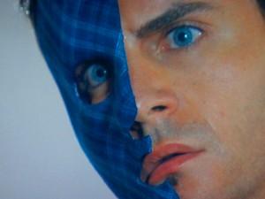 Com o rosto queimado, Fabian fica de olho no rival (Foto: Cheias de Charme / TV Globo)