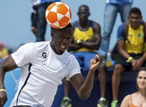 Bolt cabeceia uma bola em evento no Brasil (Foto: Buda Mendes/STF/Getty Images)