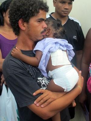Carlos Henrique com a filha no colo logo após deixar o hospital nesta terça (26) (Foto: Alba Valéria Mendonça/G1)