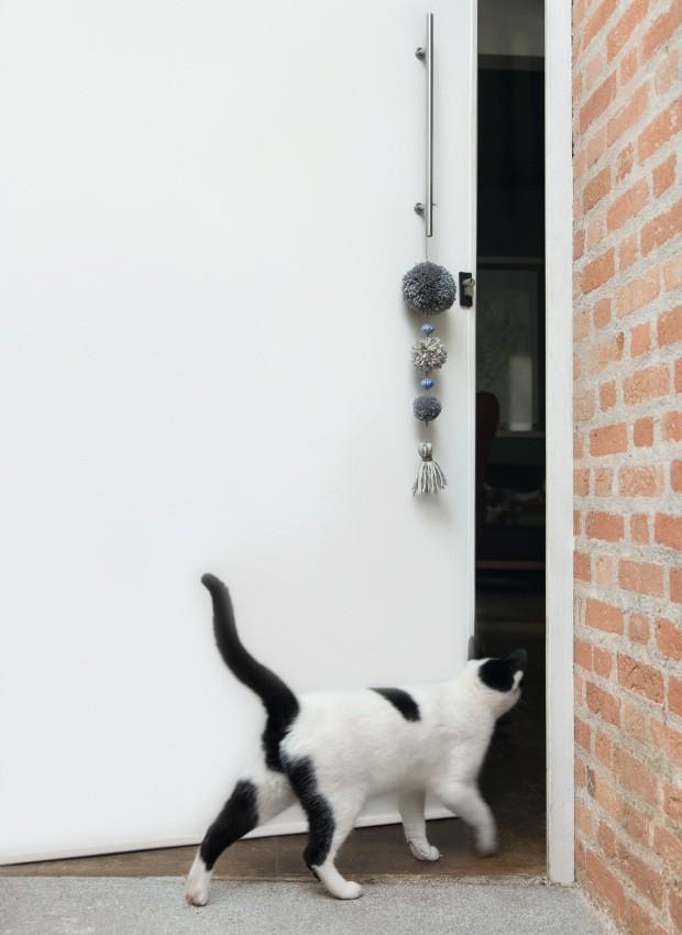 Triunfante. Não é só o gato que fica curioso para espiar: pompons coloridos, amarrados na maçaneta, são um belo passaporte de entrada (Foto: Cacá Bratke / Editora Globo)