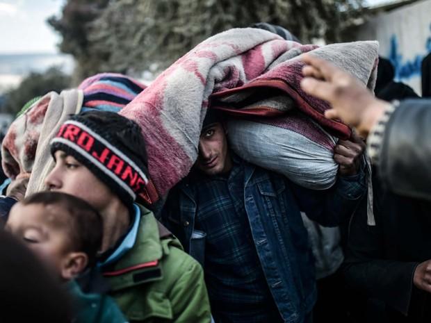 Homem carrega seus pertences na cabeça e espera perto da cidade síria de Azaz para passar para a turquia nesta sexta-feira (5) (Foto: BULENT KILIC / AFP)