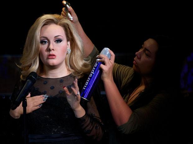 Funcionária arruma o cabelo da réplica de Adele exposta no Madame Tussauds de Londres (Foto: Andrew Cowie / AFP)