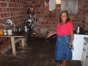 Maria mostra estrutura precária da cozinha de sua casa (Foto: Ellyo Teixeira/G1)