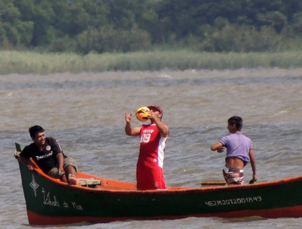 Pescador brinca com bola após pegá-la no Guaíba (Foto: Tomás Hammes / GLOBOESPORTE.COM)