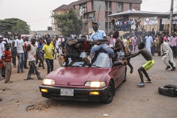 Pessoas sobem em carro para festejar o resultado das eleições presidenciais da Nigéria em Kano (Foto: AFP)
