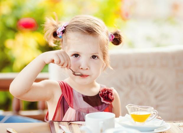 Criança tomando café da manhã (Foto: Shutterstock)