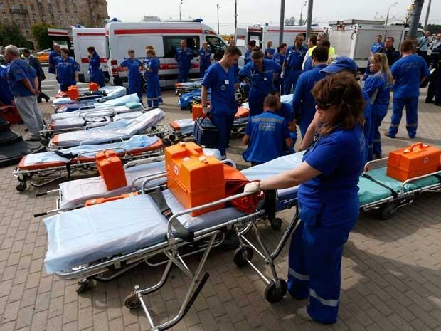 Integrantes dos serviços de emergência esperam do lado de fora de estação de metrô para atender feridos. (Foto: Sergei Karpukhin / Reuters)
