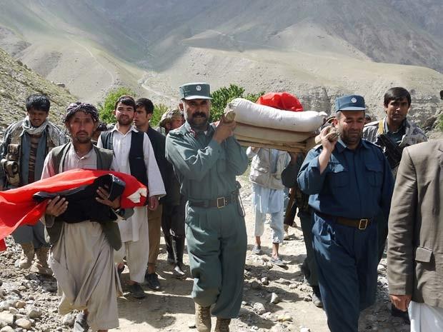 Policiais carregam corpo de vítima de enchente na província de Baghlan, região norte do Afeganistão, neste sábado (7) (Foto: AP Photo/Javid Basharat)
