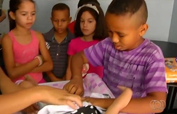 Meninos aprendem a fazer tarefas como trocar fraldas, em Goiás (Foto: Reprodução/TV Anhanguera)