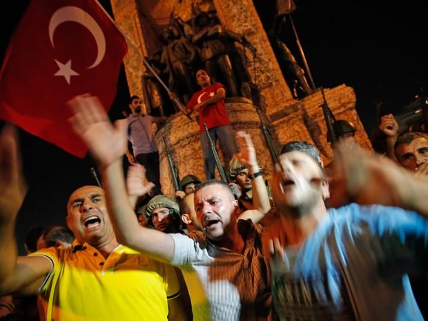Apoiadores do presidente Recep Tayyip Erdogan protestam na frente de soldados na praça Taksim em Istambul, na Turquia (Foto: Emrah Gurel/AP)