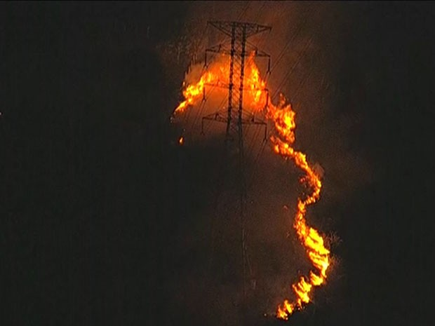 Incêndio acontecia perto de postes com fios de eletricidade (Foto: Reprodução/TV Globo)