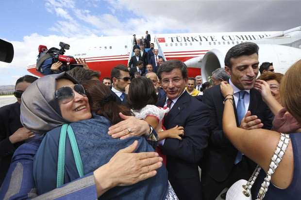 O cônsul-geral Ozturk Yilmaz (dir.), um dos sequestrados no Iraque, é recebido em Ancara por familiares junto com as outras dezenas de turcos libertados. Ao centro, o premiê turco, Ahmet Davutoglu (Foto: Hakan Goktepe/Escritório de Imprensa do Primeiro-Ministro da Turquia/Reuters)