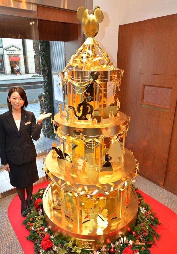 Em novembro, uma joalheria no centro de Tóquio exibiu uma 'árvore' de Natal em ouro coberta de personagens da Disney, como Mickey Mouse, Tinker Bell e Cinderela. Custando US$ 4,2 milhões (R$ 8,8 milhões), a árvore é feita de 40 quilos de ouro puro, mede cerca de 2,4 metros de altura e 1,2 metro de diâmetro. Ela é decorada com silhuetas recortadas em ouro puro de 50 personagens populares da Disney e envolta com laços feitos de folha de ouro (Foto: Kazuhiro Nogi/AFP)