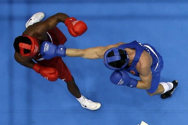 O russo Egor Mekhontcev, em azul, acerta um golpe no brasileiro Yamaguchi Falcão na semifinal do boxe (Foto: Mark Duncan/AP)