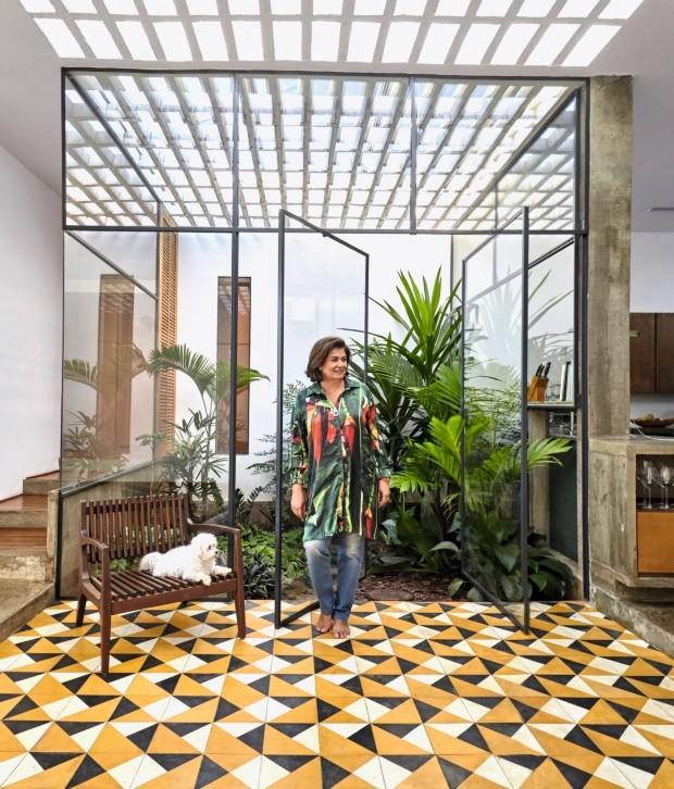 Casa tem jardim que conecta sala e cozinha, piso de ladrilho hidráulico e pérgola