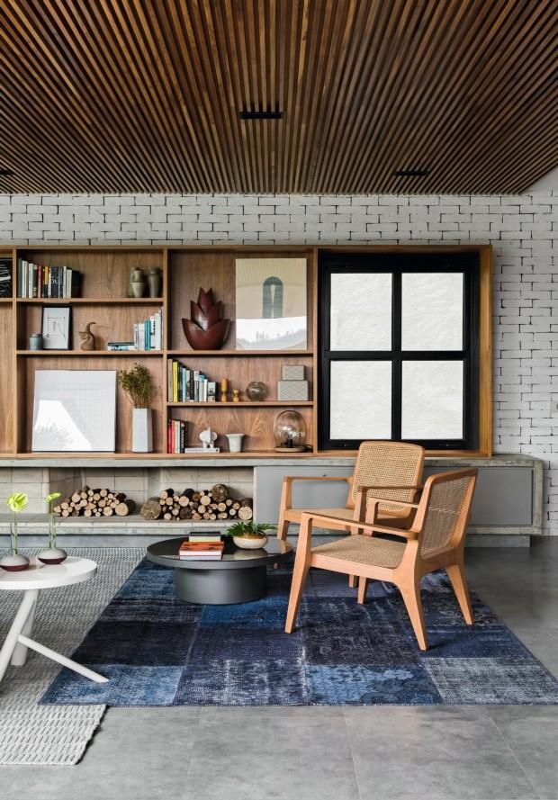 A janela ajuda a banhar de luz natural o canto da sala de estar. A pintura branca nos tijolos aparentes aumenta a claridade no ambiente e destaca na estante os objetos da Loja Teo, da Dpot Objetos e da Papel Assinado (Foto: Alain Brugier / Divulgação)