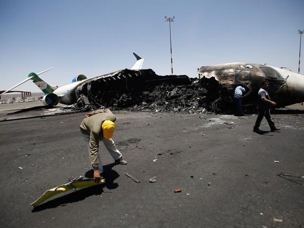 Funcionários de Felix Airways, uma companhia aérea doméstica, inspecionam um avião destruído por ataques aéreos liderados por sauditas no aeroporto International de Saná, no Iêmen (Foto: Hani Mohammed/AP)