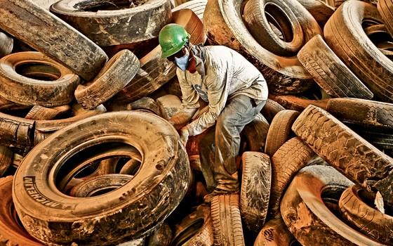 Funcionário da Votorantim  leva pneus para queimar nos fornos de cimento  (Foto: Alex Almeida/ Editora Globo)