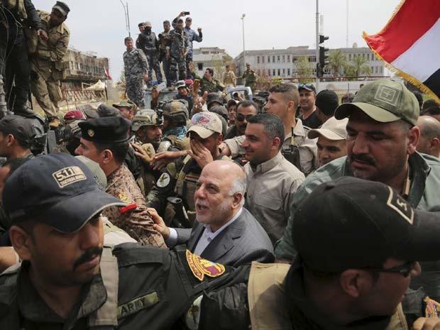 O premiê iraquiano Haidar al-Abadi anda pela cidade de Tikrit nesta quarta-feira (1º) depois que as forças de segurança recuperaram o controle dos jihadistas do Estado Islâmico (Foto: REUTERS/Stringer)