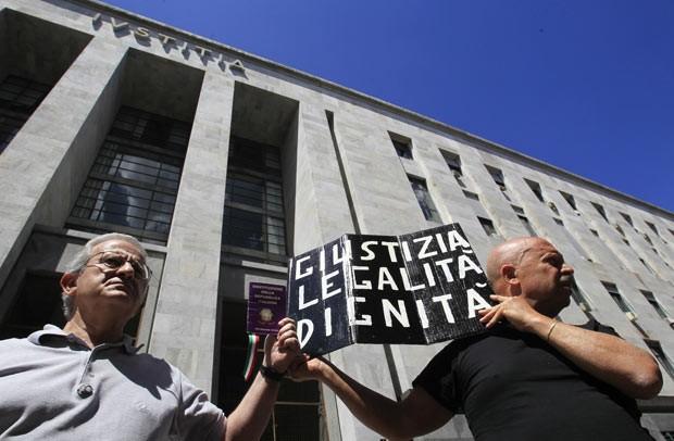 Com cartaz com os dizeres 'justiça, legalidade e dignidade', italianos esperam o resultado do julgamento de Silvio Berlusconi, nesta segunda-feira (24), em frente ao Tribunal de Milão (Foto: AFP)