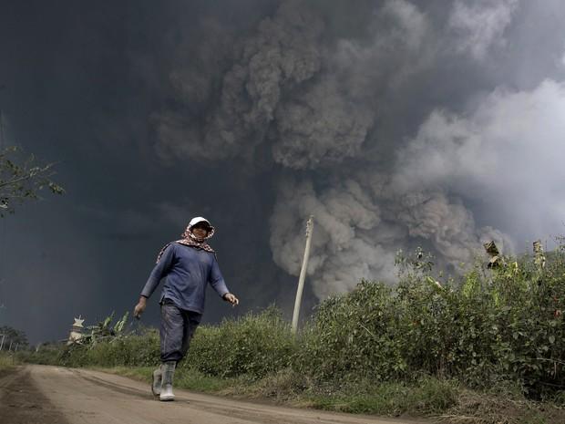 Habitante da ilha ocidenteal de Sumatra corre após o vulcão Monte Sinabung entrar em erupção neste sábado (1), na Indonésia (Foto: S Aditya/Reuters) (Foto: CHAIDEER MAHYUDDIN / AFP)