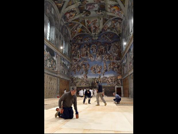 Foto fornecida pelo jornal 'L'Osservatore Romano' mostra trabalhadores elevando o piso da Capela Sistina, no Vaticano. Cardeais definiram que o conclave começará na terça-feira (12). (Foto: L'Osservatore Romano/AP)