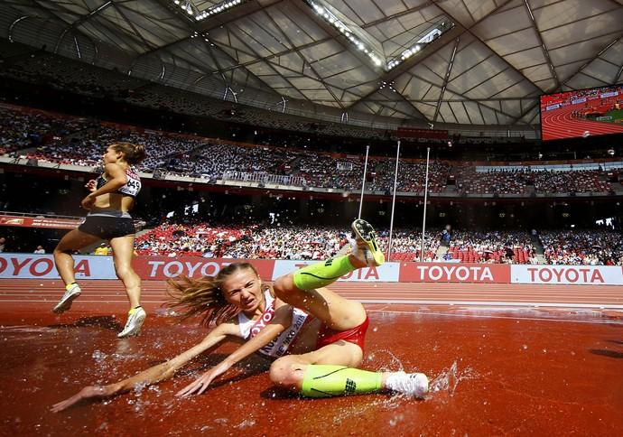 Sviatlana Kudzelich sofre uma queda no fosso dos 3.000m com obstáculos (Foto: Reuters)