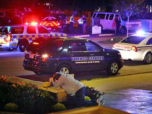Um homem se ajoelha em frente a igreja atacada (Foto: Wade Spees / The Post e Courier / via AP Photo)